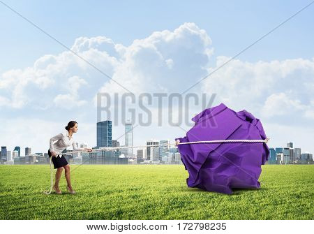 Young woman outdoors making huge paper ball move with rope.