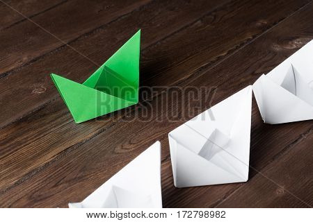 Set of origami boats on wooden table, one green and the rest are white.
