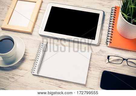 Still life photo of tablet, notepad, coffee and glasses on wooden table.