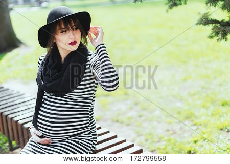 Pregnant girl in striped dress and black hat. Looking aside. Sitting in park, outside. Pregnant, woman