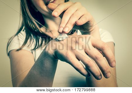 Smiling young woman applying cream on her hands - skin care concept - retro style