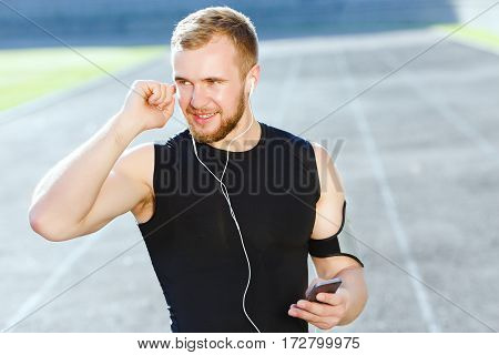 Man taking stop after running on track, looking aside. Waist up of sportsman in black training suit listening to music. Outdoors, stadium