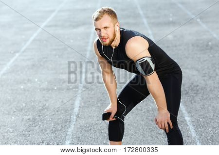 Man taking stop after running on track, bending ahead. Full body of sportsman in black training suit and red sneakers listening to music. Outdoors, sunlight, stadium