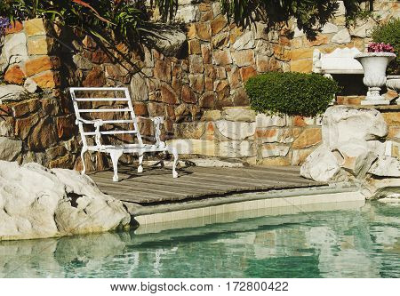 Retro Sun Bed On The Edge Of A Blue Swimming Pool The Rocks,of The Concept Of Travel, Selective Focu