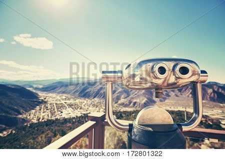 Color toned photo of binoculars looking out over a valley selective focus Glenwood Springs Colorado USA.