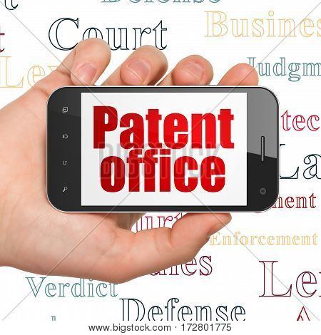 Law concept: Hand Holding Smartphone with  red text Patent Office on display,  Tag Cloud background, 3D rendering