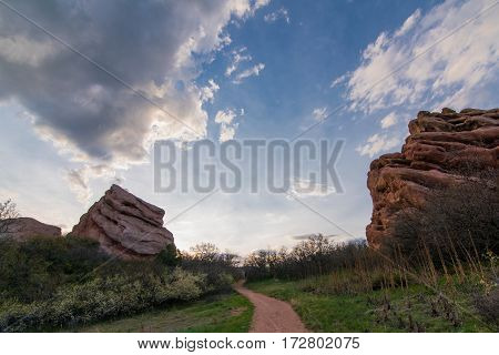 Image of a trail leading to red rock formations on a cloudy day.