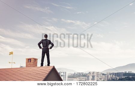 Young determined businessman standing on house roof and looking away. Mixed media