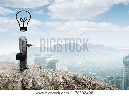 Businessman outdoor with suitcase and light bulb instead of head.