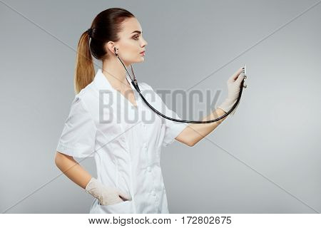 Gorgeous nurse with nude make up wearing white medical robe and holding stethoscopes at gray background, health care and pharmacology concept, girl on white uniform.