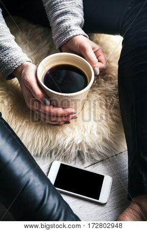 beautiful stylish girl in leather trousers and a modern sweater sitting on the floor with a cup of coffee and mobile phone