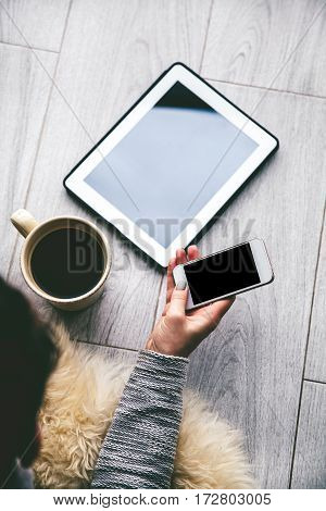 Women's hands holding a large cup of coffee. Nearby is an electronic tablet with a smartphone