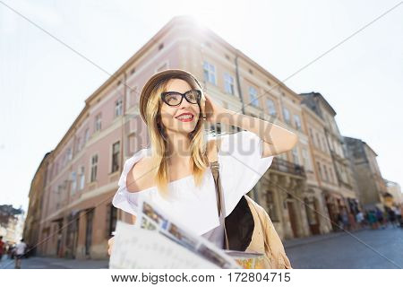Attractive  tourist girl with light hair and red lips wearing hat and glasses, holding map at old European city background, sunny weather.