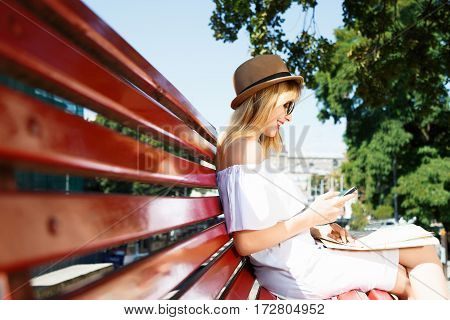 Tourist girl with light hair and red lips wearing hat and glasses, holding map and mobile phone at old European city background and smiling, sitting on bench.