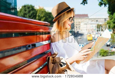 Pretty girl with light hair and red lips wearing hat and glasses, holding map at old European city background and smiling, sitting on bench.