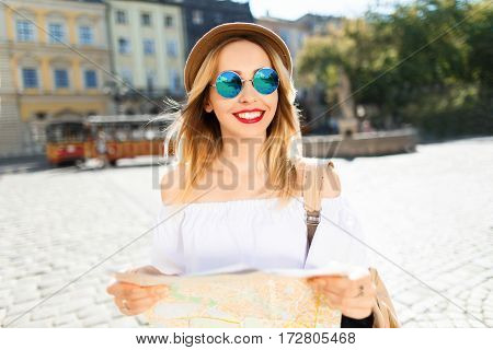 Nice tourist girl with light hair and red lips wearing hat and glasses, holding map at old European city background, portrait.
