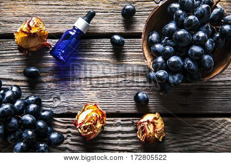Essential oil of grape vine blue grapes old wooden background fruit. food