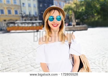 Lovely tourist girl with light hair and red lips wearing hat and glasses, standing at old European city background and smiling.