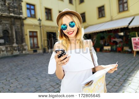 Attractive tourist girl with light hair and red lips wearing hat and glasses, holding map and mobile phone at old European city background and smiling.