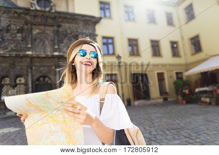 Happy tourist girl with light hair and red lips wearing hat and glasses, holding map at old European city background and smiling.