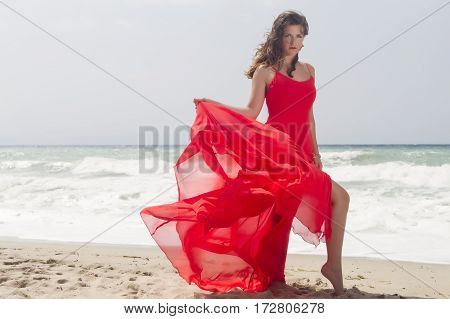 Portrait Of Beautiful Woman In Red Dress In Front Of The Beach.