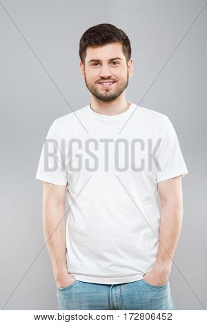 Man with beard in white T-shirt and jeans. Mockup. Standing straight, smiling. Hands in pockets. Indoors, studio