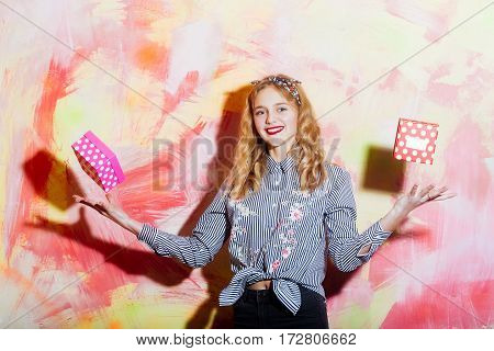 Cheerful Girl Throws Two Red And Pink Polkadot Gift Boxes
