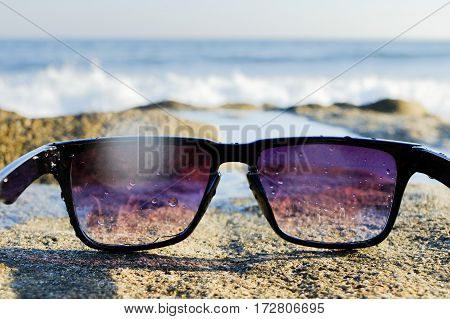 Black sunglasses lying on rock near the sea, copy space, close up, summertime.