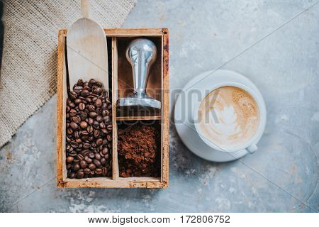 Coffee beans tamper and a cup of delicious coffee