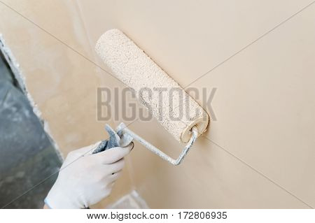 Painting roller in a man's hand painted wall.