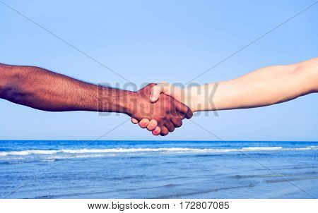 Handshake between black hand of african migrant and white american man on blue sky background - Current concept of policies on refugees reception humanitarian aid and world peace