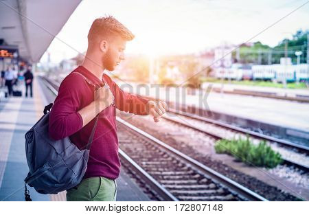 Young man checking the time on wristwatch at rail station platform - Student commuter waiting train at railway departures in pensive facial expression - Everyday lifestyle concept
