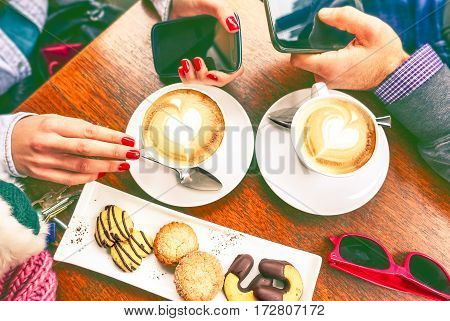 Friends drinking coffee holding smart phone at cafe bar top view image -Young couple having breakfast date with latte heart shape cappuccino and cookies on wooden table - Modern concept of relations