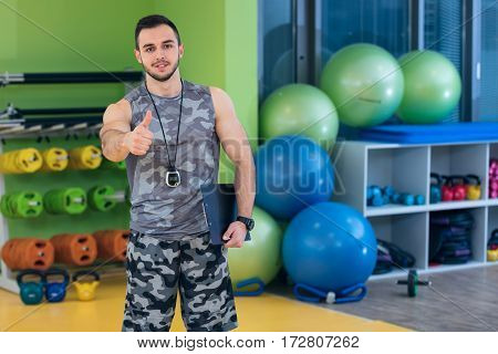 Portrait of a muscular trainer showing thumbs up