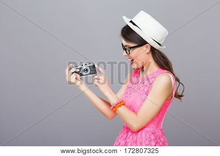 Cute young girl with dark hair and red lips wearing pink dress and sunglasses posing with camera at gray studio background.
