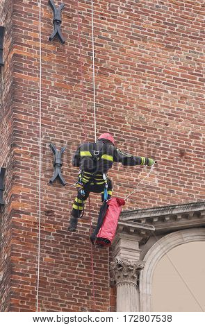 Fireman Climbing With Ropes And Climbing Equipment On An Old Bui
