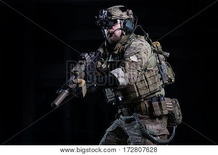SWAT officer with rifle in hands in helmet with night vision devices and other military equipment