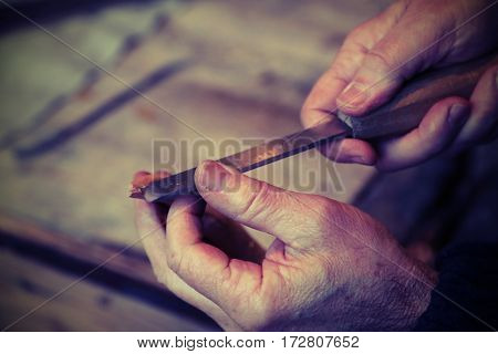 Hands Of An Elderly Carpenter While The Piece Of Wood With A Chi