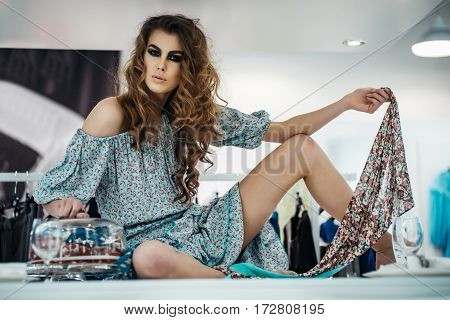 Pretty Girl Sits On Table In Closing Shop