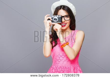 Gorgeous young girl with dark hair and red lips wearing pink dress and sunglasses posing with camera at gray studio background.