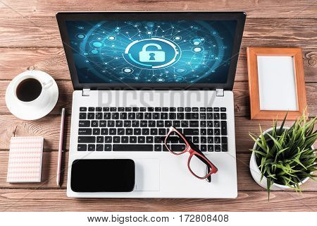 Business workplace with office stuff and laptop with padlock icon on screen