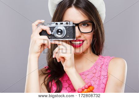 Smiling young girl with dark hair and red lips wearing pink dress and sunglasses posing with camera at gray studio background, portrait.