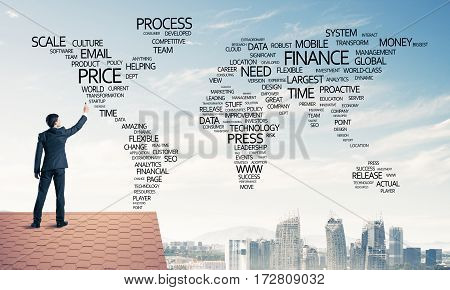 Young businessman standing on house roof and writing business related words. Mixed media