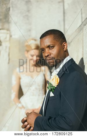 Handsome Bearded African American Groom Touches Wedding Ring On Finger
