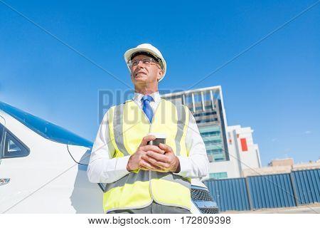 Senior engineer man in suit and safety helmet outdoor having coffee.