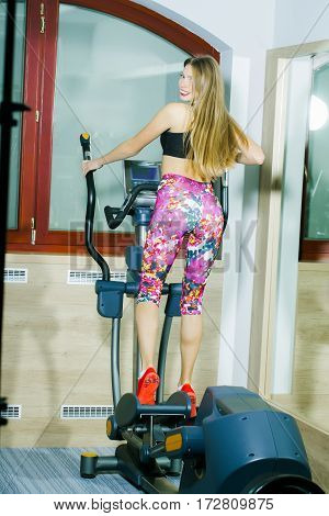Pretty girl or beautiful smiling woman with long blond hair in pink sportswear with fit slim sexy body exercises on cross trainer. Fitness gym workout