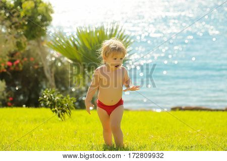 Cute surprised baby boy with blond hair in red trunks walks on green grass outdoors on idyllic sunny summer day on blue sea background