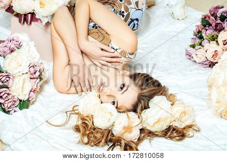 Sexy young pretty woman or cute girl with long hair in floral dress laying among lilac rose and peony flowers on white bedsheet