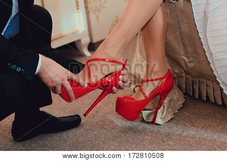 A man in a suit takes off his shoes from the feet of a woman