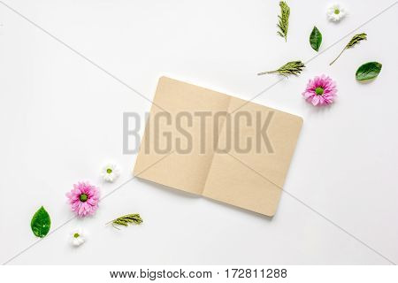 Flower petals and brown craftpaper copybook on white table background top view mock up